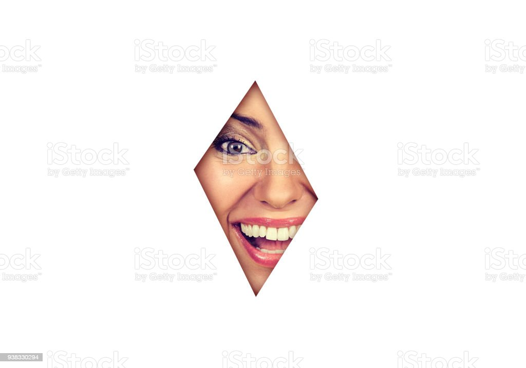 Beautiful surprised woman laughing looking though the gap in white background at camera stock photo