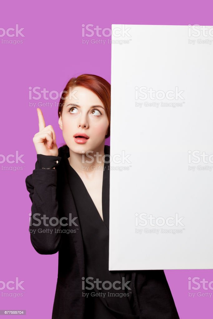 beautiful surprised young woman with big empty poster on the wonderful purple background royalty-free stock photo