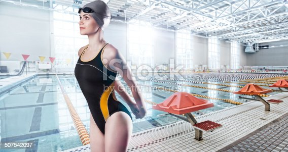 Attractive Young Female Model posing in a one-piece competition Swimsuit with Cap and Goggles against invented pool background