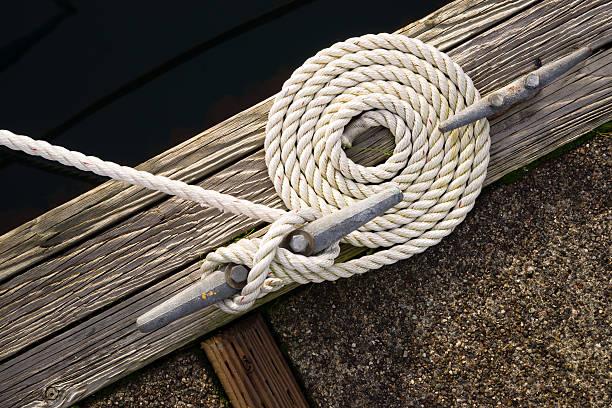 beautiful swirled curled rope boat bow line nautical tie down - aangemeerd stockfoto's en -beelden