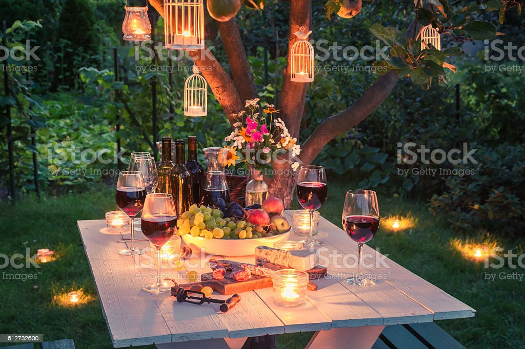 Beautiful table full of cheese and meats in garden stock photo