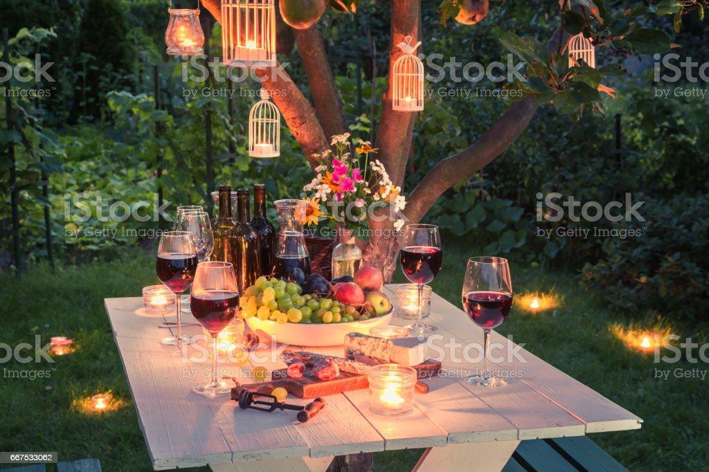 Mesa linda cheia de vinho, queijo e petiscos ao entardecer - foto de acervo