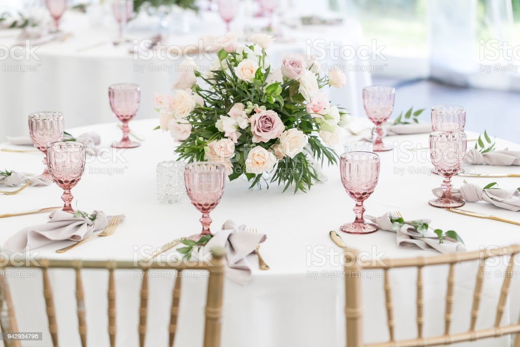Beautiful table setting with crockery and flowers for a party, wedding reception or other festive event. Glassware and cutlery for catered event dinner. stock photo