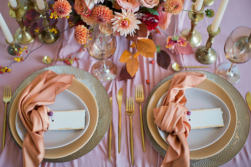 Beautiful table setting with autumn flowers, orange and pink napkins and burning candles. Autumn wedding concept