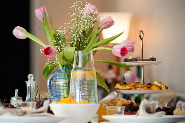 beautiful table topped with flowers and meals for big family dinner - manonallard stock photos and pictures