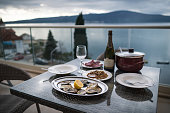 Beautiful table with local food and wine on the home balcony. Focus on oysters. Background of sea and mountains. Oysters with lemon, meat, snacks and bottle of sparkling wine. Still life
