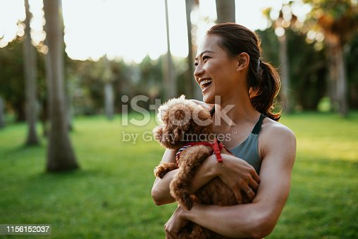Exercising yoga outdoors in park and nature in Asia. Millennial generation woman in sport clothing with dog in the park