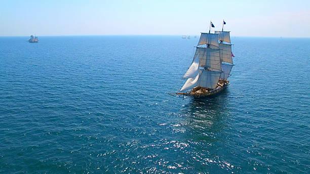 Beautiful tall ship sailing deep blue waters toward adventure stock photo