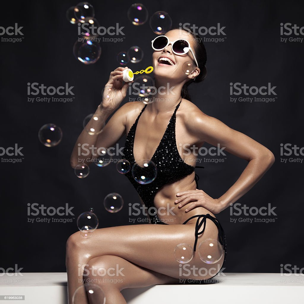 Beautiful Tan Female Model Posing In Bikini And Blow Bubbles. stock photo