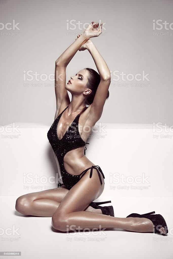 Beautiful tan female model posing in bikini and shoes stock photo