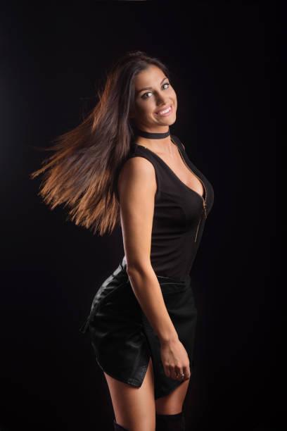 beautiful tan female model posing in leather skirt, hair flick - damen rock braun stock-fotos und bilder