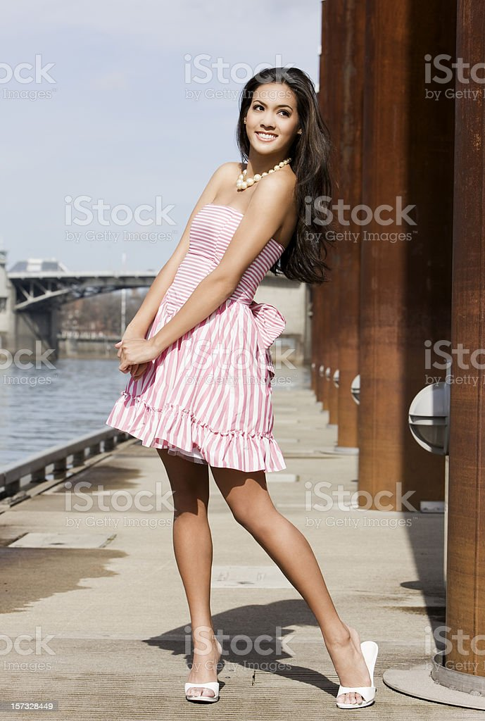 Beautiful Tan Young Woman in Pink Striped Dress on Pier stock photo