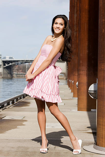 beautiful tan young woman in pink striped dress on pier - mini dress stock photos and pictures