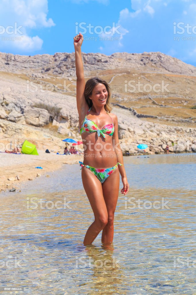 Beautiful Tanned Girl In A Bikini Standing In A Water And Raising Hand In Air