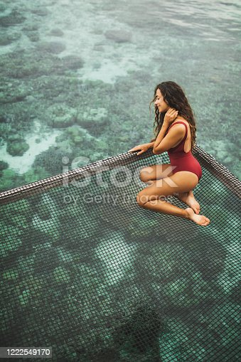 817409212 istock photo Beautiful tanned woman in red swimsuit relaxing in over-reef hammock with amazing view of coral reef in transparent water. Vacations in Asia concept, tropical background. 1222549170
