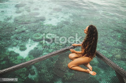 817409212 istock photo Beautiful tanned woman in red swimsuit relaxing in over-reef hammock with amazing view of coral reef in transparent water. Vacations in Asia concept, tropical background. 1222549172