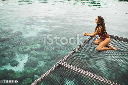 817409212 istock photo Beautiful tanned woman in red swimsuit relaxing in over-reef hammock with amazing view of coral reef in transparent water. Vacations in Asia concept, tropical background. 1236469110