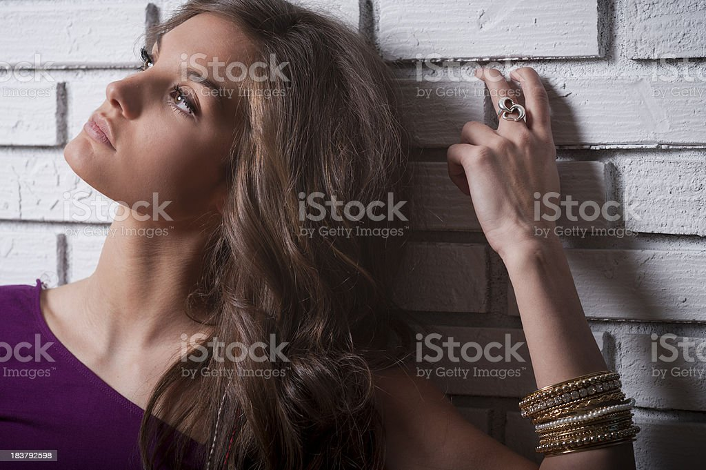 Beautiful tanned woman leans against white brick stock photo