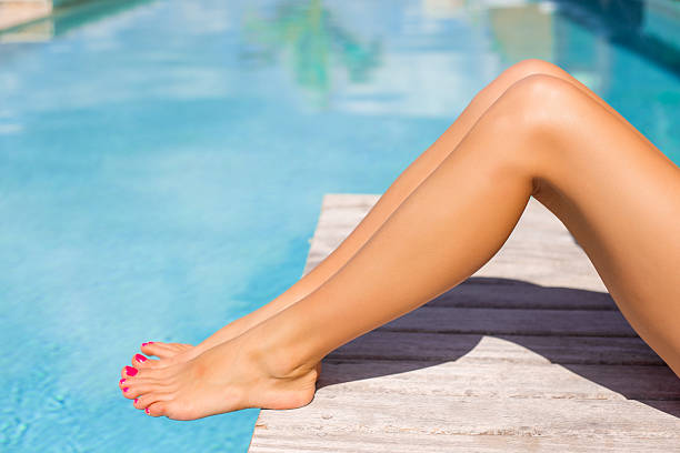 Beautiful tanned women legs by the pool stock photo
