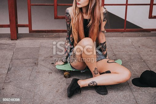 The body of attractive slim girl with tattoos. Young beautiful female model sitting on a green longboard in cloudy weather. Alternative lifestyle concept