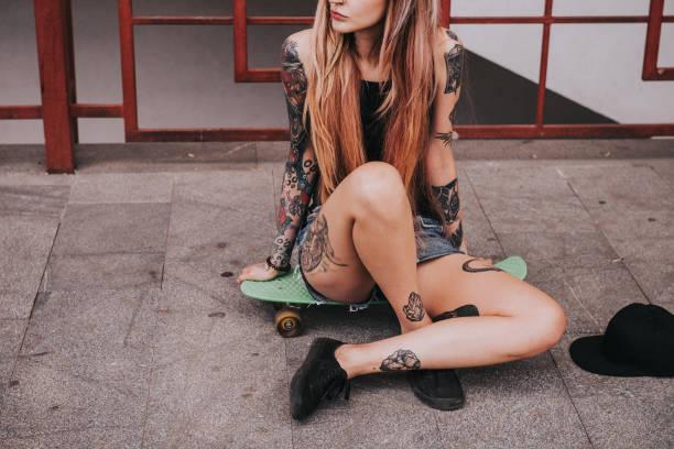 スケート ボードで美しい刺青の女の子 - スケートボードをする ストックフォトと画像