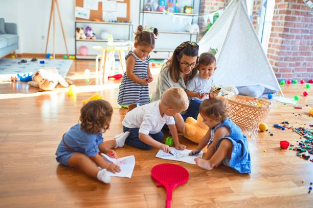 Beautiful teacher and group of toddlers sitting on the floor drawing using paper and pencil around lots of toys at kindergarten stock photo