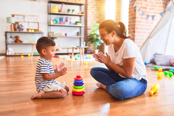 Beautiful teacher and toddler boy building pyramid with hoops bolcks at kindergarten stock photo