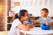 Beautiful teacher and toddler boy playing with vintage blue phone at kindergarten