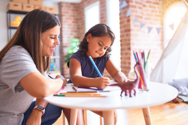 Beautiful teacher and toddler girl drawing draw using colored pencils at kindergarten Beautiful teacher and toddler girl drawing draw using colored pencils at kindergarten preschool teacher stock pictures, royalty-free photos & images