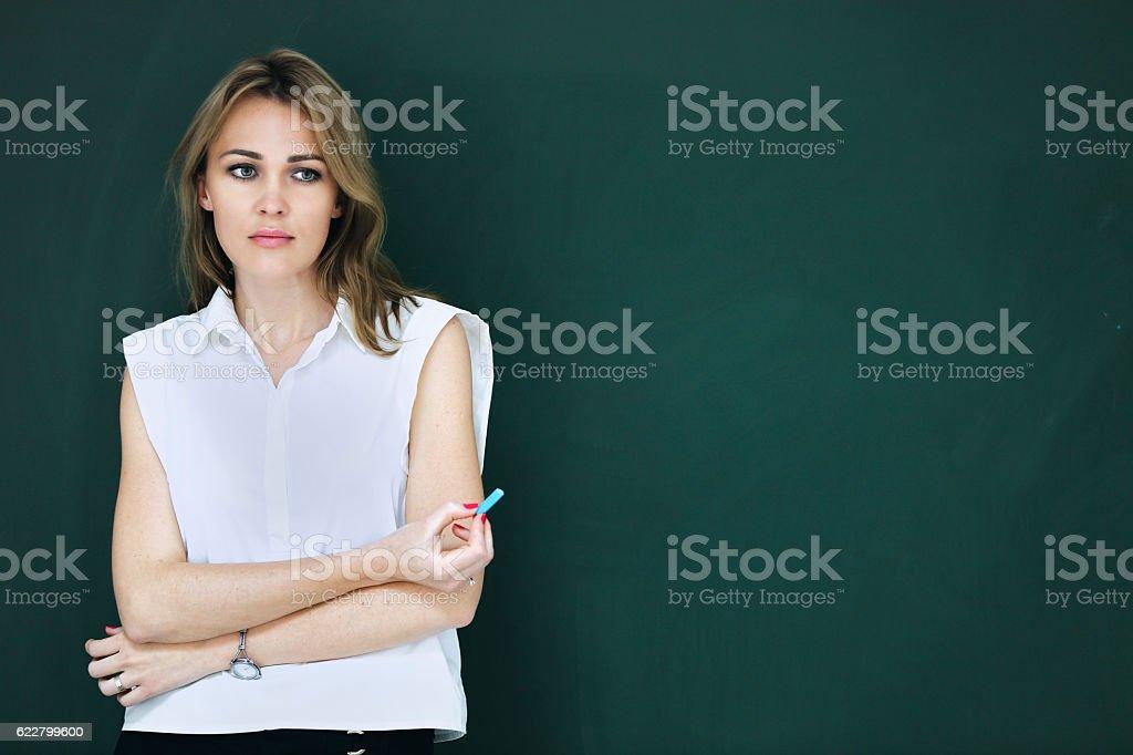 Beautiful teacher at blackboard stock photo