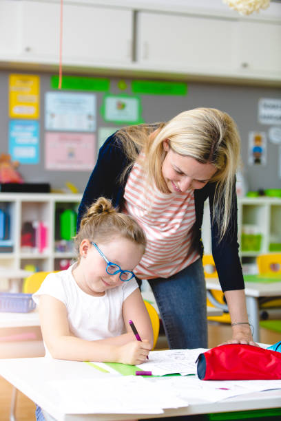 beautiful teacher helps her student to learn stock photo