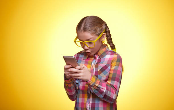 Beautiful teen girl is surprised playing with the phone Emotional teenager, the little girl plays with the phone, children's emotions, girl with glasses, bright checkered shirt, portrait of a young girl nerd hairstyles for girls stock pictures, royalty-free photos & images