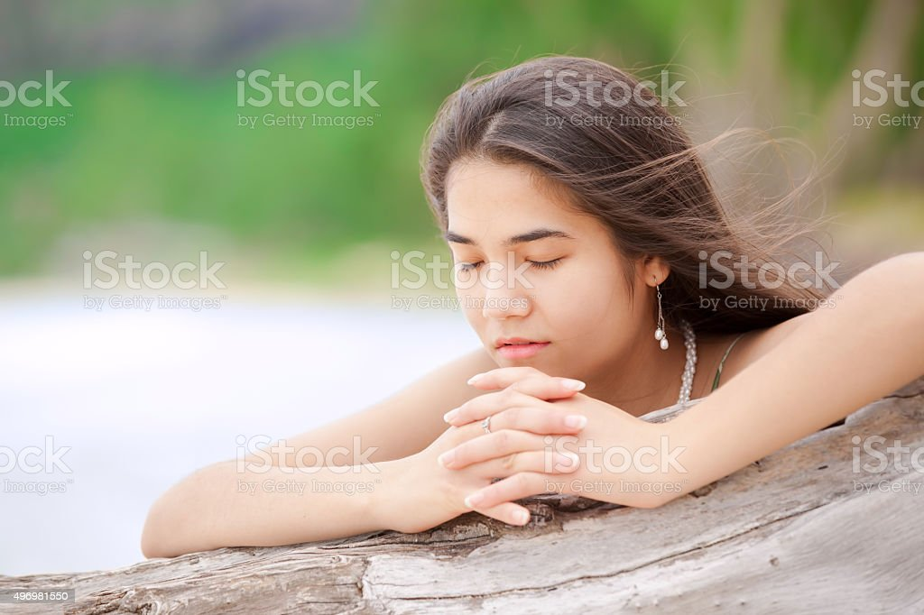 Beautiful teen girl on beach praying by driftwood log stock photo