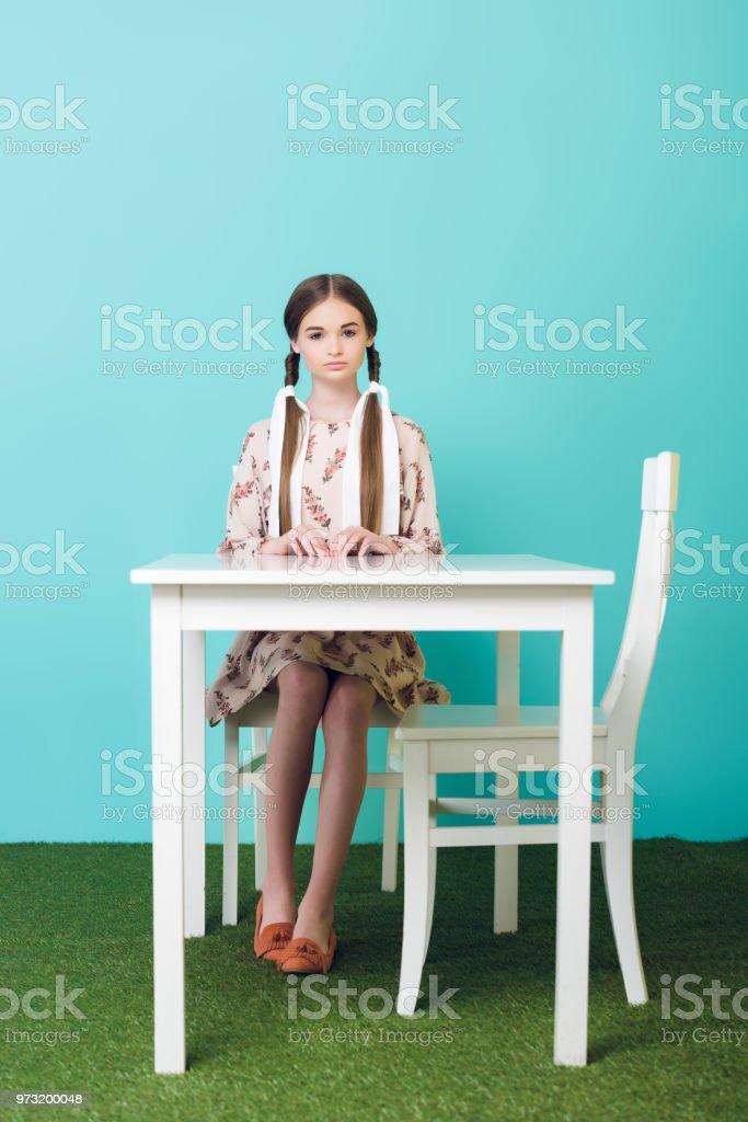 linda menina adolescente com tranças sentado na mesa, azul - foto de acervo