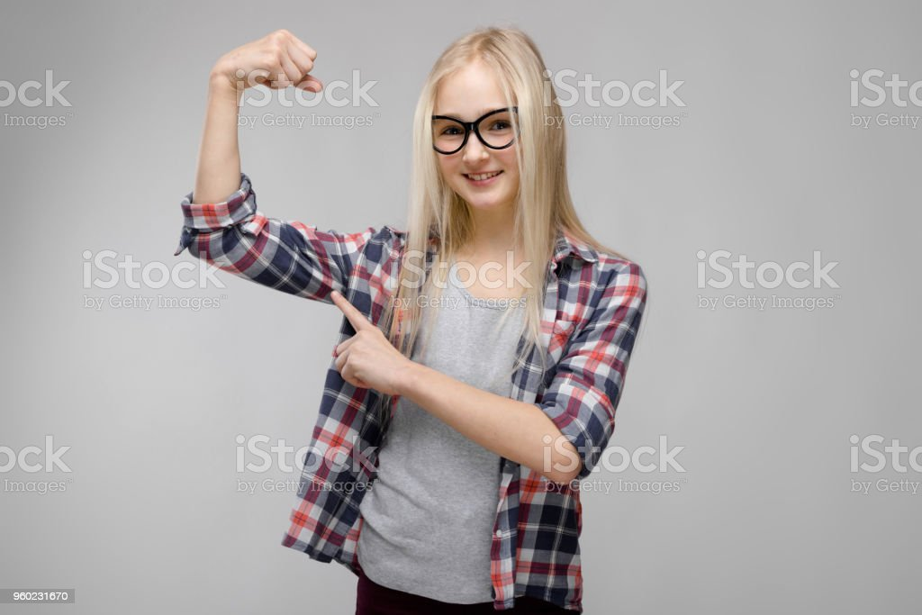 ae1a06fb805 Beautiful teen girl with long hair and wearing glasses. A teenage girl in a  plaid shirt and a gray T-shirt. A teenage girl is pointing a finger at a  muscle ...