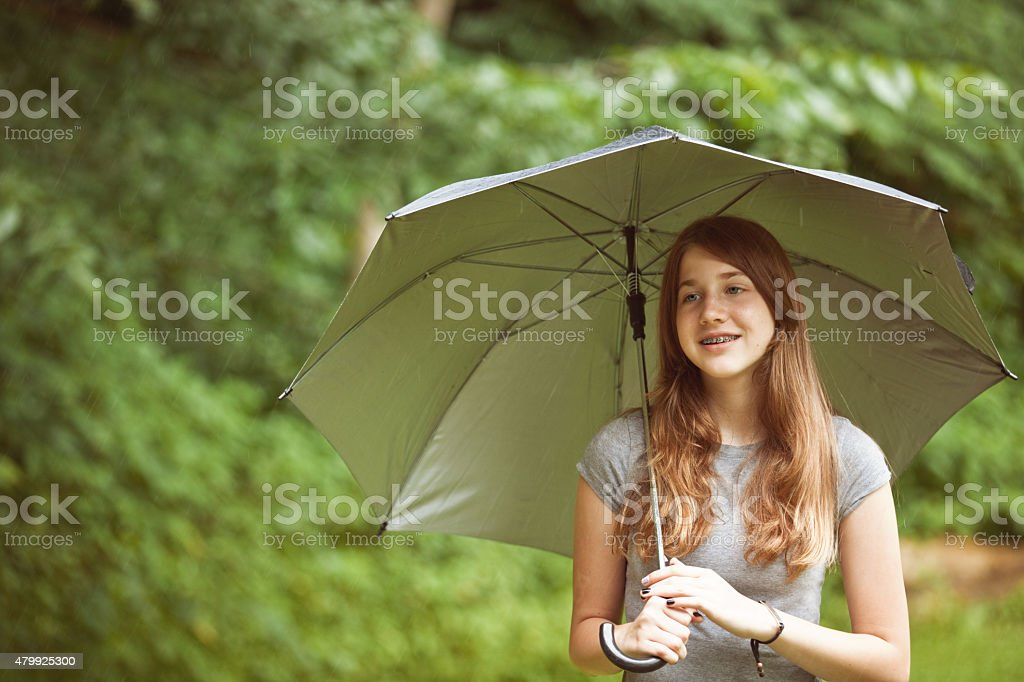 A beautiful 13 year old girl outdoors with an umbrella on a rainy...