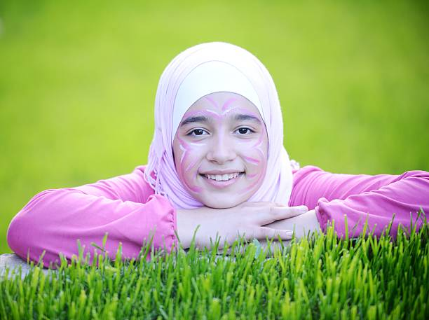 beautiful teenage arabic girl lying on green grass in nature - arabic girl stock photos and pictures