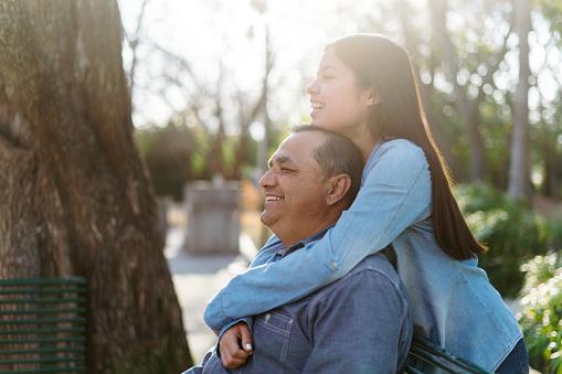 Beautiful latin teenage girl embracing father at park, looking away and smiling.