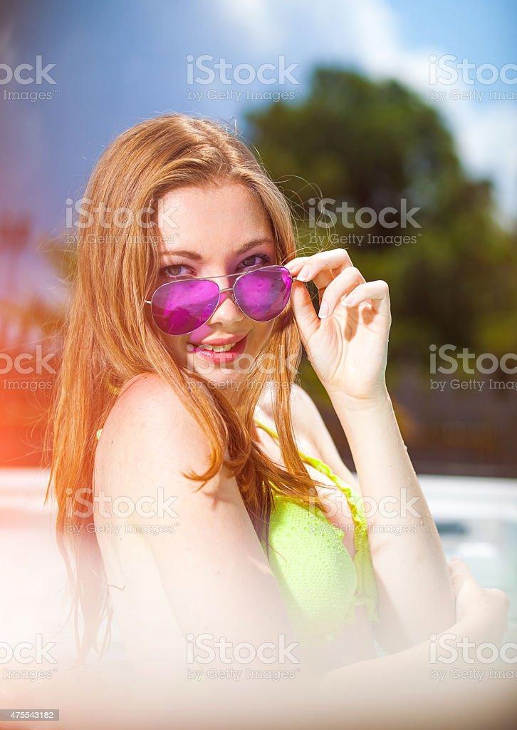 Beautiful teenage girl at the swimming pool stock photo