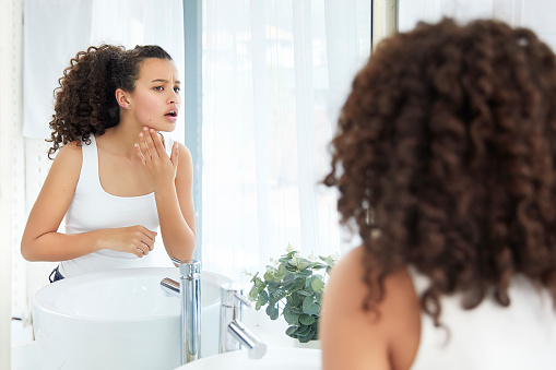Female Skin Care. Beautiful young girl touching her face and sees a pimple looking in the mirror in bathroom