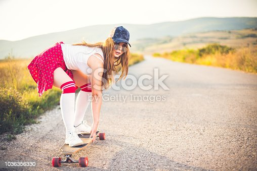 Beautiful teenage girl driving skateboard on a sunny summer day outdoors