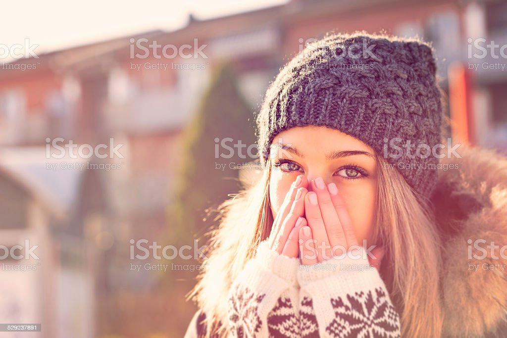 Beautiful teenage girl heats up hands stock photo