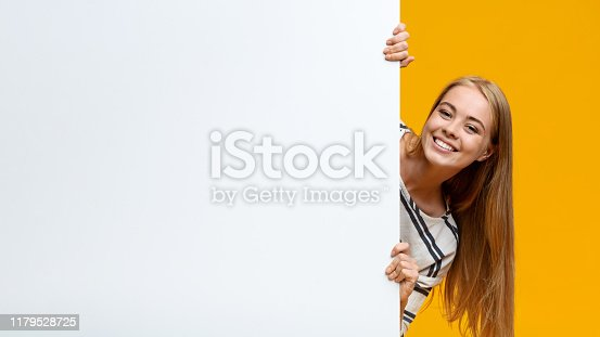 Cute teenage girl looking out of white blank placard for your text or product, yellow background