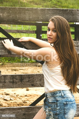 Beautiful teenage girl, opening a gate of a corral in a farm, and looking at the camera.