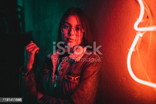 Portrait of beautiful casual dressed teenage girl standing next to neon light at night