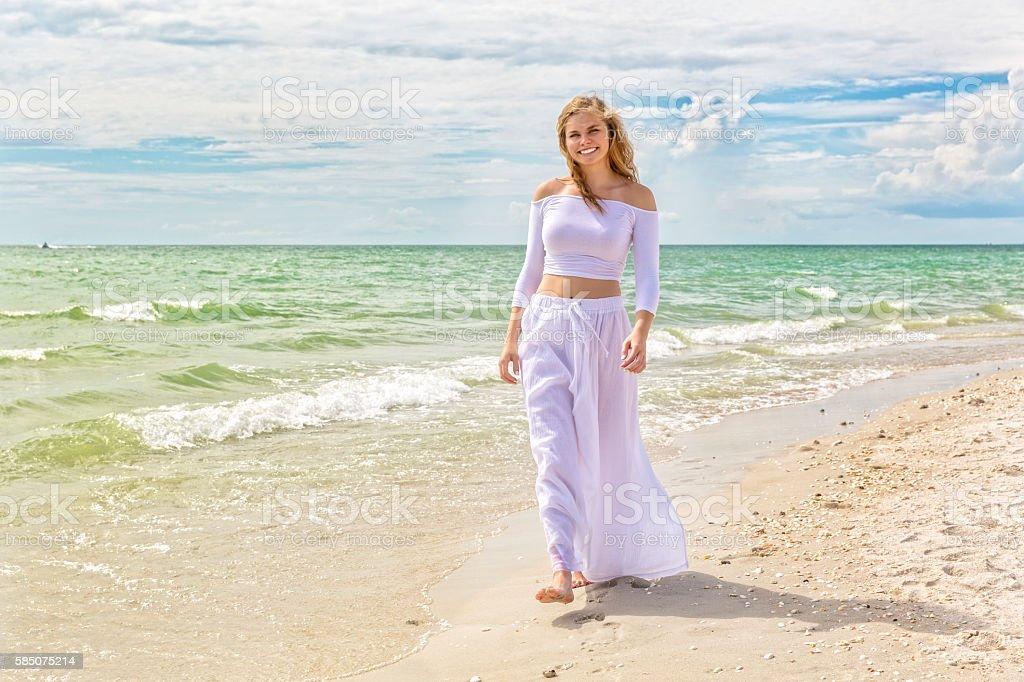 Beautiful Teenage Girl Walks Along the Beach stock photo