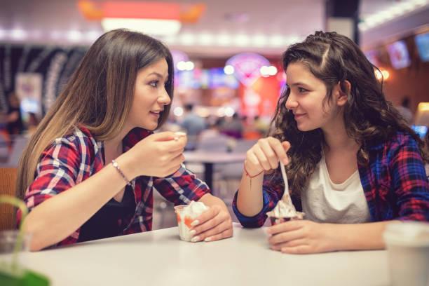 Schöne Teenager-Mädchen essen Eis im Restaurant – Foto