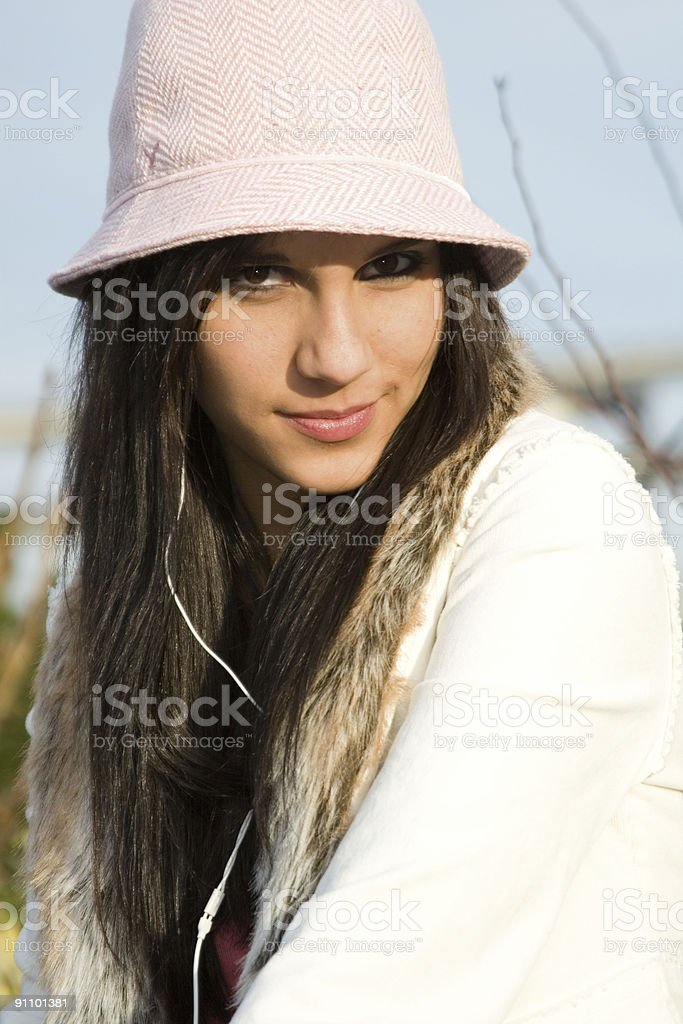 Beautiful Teenage Young Woman Portrait in Hat Wearing Earbuds stock photo