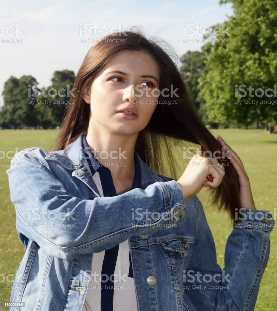 Beautiful teenager Bulgarian outdoor girl brushing hair action stock photo
