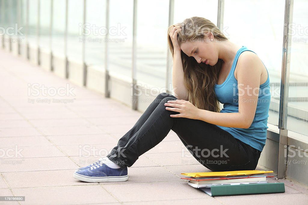 Beautiful teenager girl depressed sitting on the floor outdoor royalty-free stock photo